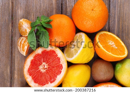 Fresh citrus fruits with green leaves on color wooden background - stock photo