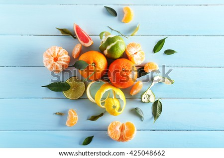 Fresh citrus fruits with green leaves on wooden background - stock photo
