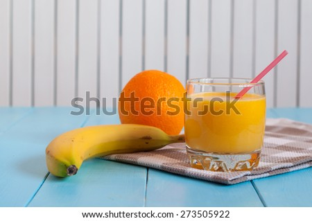 Fresh citrus juices with banana and orange on white wooden background. Healthy food, - stock photo