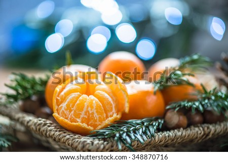 Fresh Clementines or Tangerines in the Basket on Brown Wooden Table with Xmas Lights and Tree Branches - stock photo