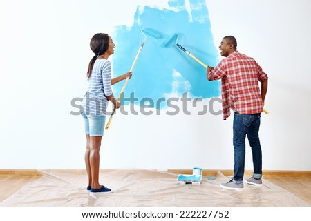 Fresh coat of paint on new apartment for young black african couple who have success and a home - stock photo
