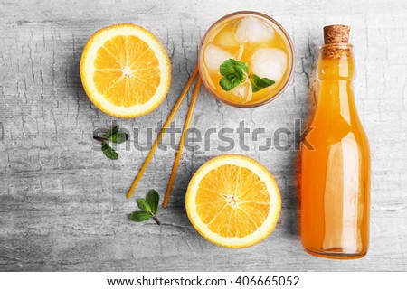 Fresh cocktail preparation: soda bottle, slices of an orange,  mint on grey table background, top view - stock photo