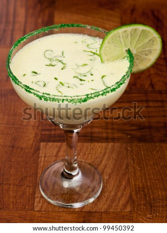 fresh cocktail served on a bar top garnished with green sugar and a lime wheel - stock photo