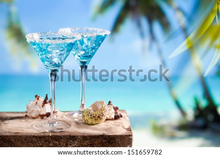 Fresh cocktail with blue curacao on beach background - stock photo