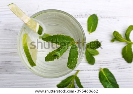 Fresh cocktail with ice, scattered mint and lime on white wooden table background