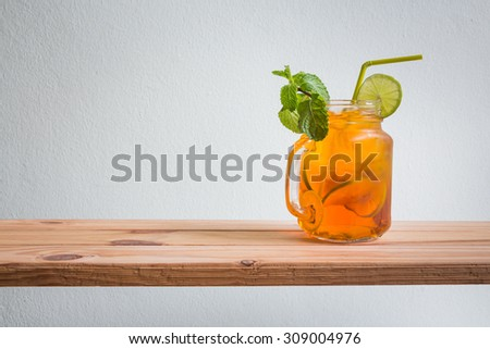 Fresh cocktail with lemon tea on wooden counter bar, rustic style - stock photo