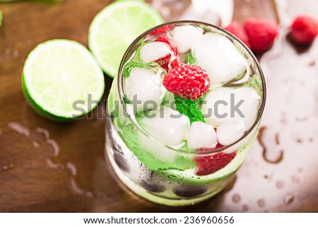 Fresh cocktail with mint and berries on the brown table - stock photo