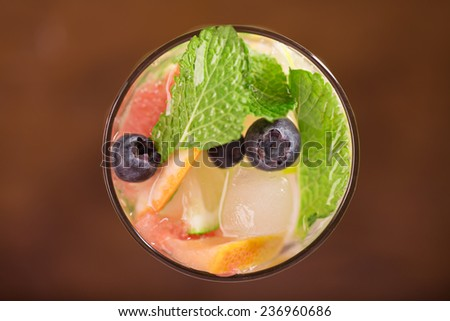 Fresh cocktail with mint, grapefruit and berries on the table - stock photo