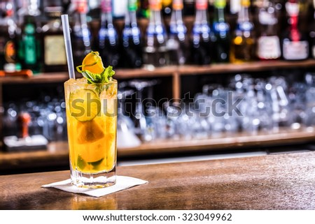 Fresh cocktail with orange, limet, mint and ice. Alcoholic, non-alcoholic drink-beverage at the bar counter in the night club. - stock photo