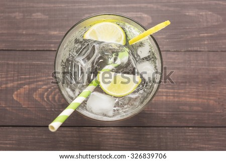 Fresh cocktail with soda, lime on a wooden background. - stock photo