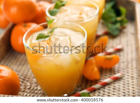 Fresh cocktails with ice, mint and tangerines on a wicker tray, close up - stock photo