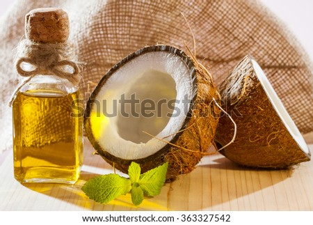 Fresh coconut, bottle of oil and mint leaf on wooden table - beautiful skincare and haircare composition