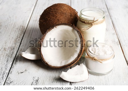 Fresh coconut oil in glassware on color wooden table background - stock photo