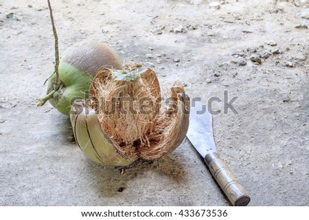 Fresh coconut peeling. Shelling coconut with heavy chop knife for juice - stock photo