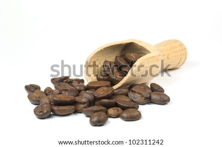 Fresh coffee beans and scoop on a white background