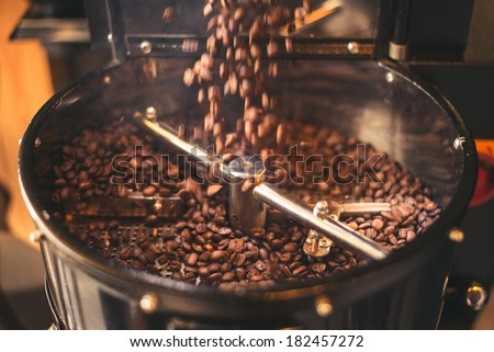 Fresh Coffee Beans - Freshly roasted 100% Arabica coffee beans falling into a spinning cooler professional machine. - stock photo