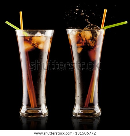 fresh cola juice and ice cubes splash in a glass on black background - stock photo
