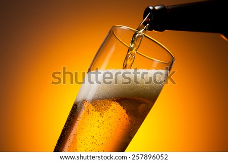 fresh cold beer is pouring in to a glass with dew drops - stock photo