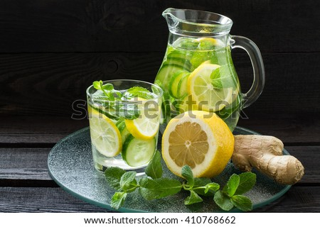Fresh cold water with lemon, cucumber, ginger, mint and ice in a pitcher and glass on a glass tray - stock photo