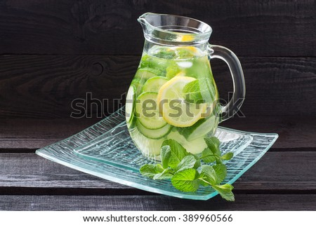 Fresh cold water with lemon, cucumber, ginger, mint and ice in a pitcher on a glass tray - stock photo