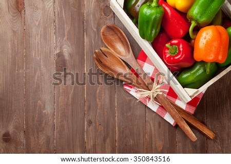 Fresh colorful bell pepper box on wooden table. Top view with copy space - stock photo