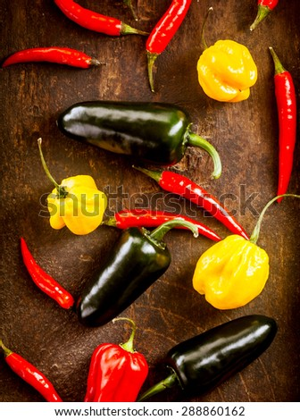 Fresh colorful red chili peppers and habanero with yellow sweet bell pepper scattered on a wooden table viewed from overhead - stock photo