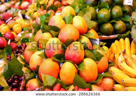Fresh colorful tropical mango on display at farmers fruits market - stock photo