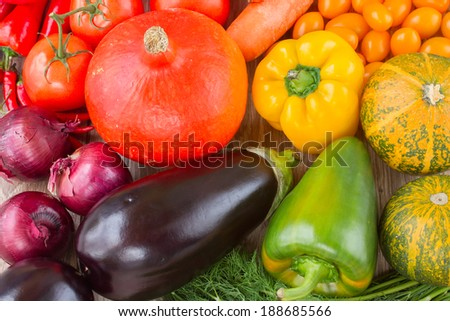 fresh colorful vegetables on table - pumpkin, tomatoes, peppers, eggplant and onion - stock photo