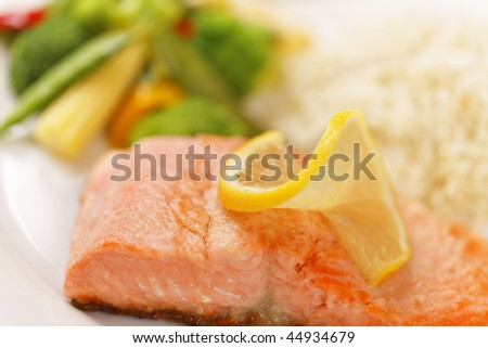 fresh cooked salmon filet meal with vegetables and rice on the side. Very shallow depth of field. - stock photo