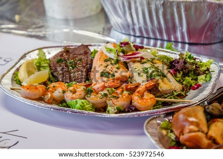 Fresh cooked seafood with lobster, shrimps, lemon, herbs, oil, vegetables and spices on dish, side view.