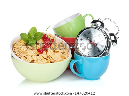 Fresh corn flakes with currant, alarm clock and colorful cups. Isolated on white background