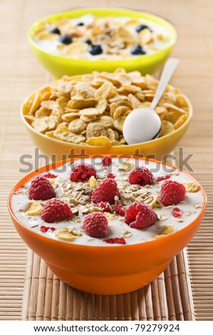 Fresh corn flakes with raspberries and milk close up - stock photo