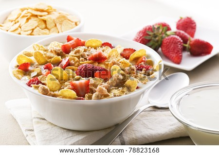 Fresh corn flakes with strawberries and milk close up - stock photo