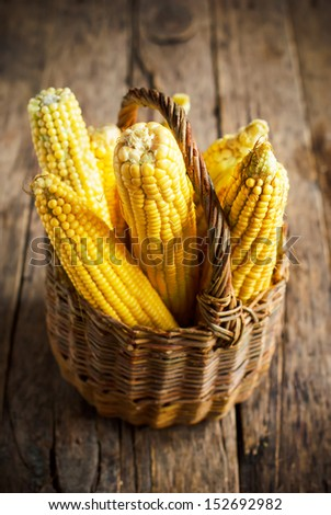 Fresh Corn in Basket on the wooden table, selective focus - stock photo