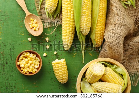 Fresh corn on cobs on green wooden table, top view - stock photo