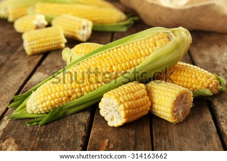 Fresh corn on cobs on rustic wooden table, closeup - stock photo