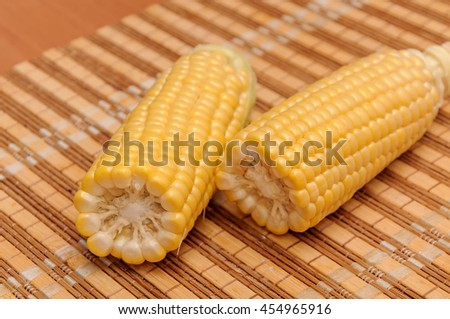 Fresh corn on cobs on rustic wooden table, closeup. - stock photo