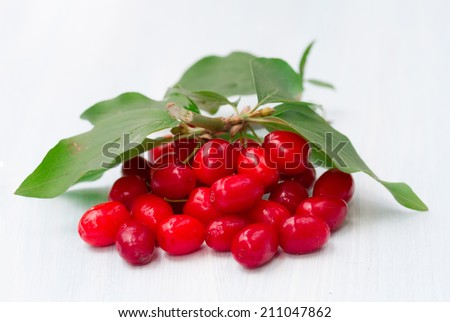 fresh cornel berries on a wooden background