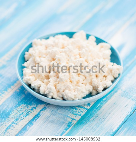 Fresh cottage cheese in a saucer, close-up - stock photo