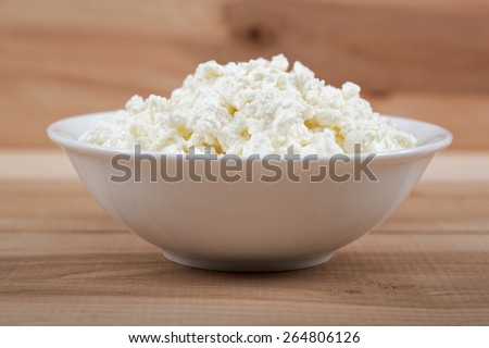 Fresh cottage cheese in a white bowl on a wooden table. - stock photo