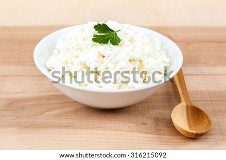 Fresh cottage cheese in a white bowl with spoon on a wooden table.