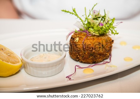Fresh crab cake with sauce and half lemon garnished with greens - stock photo