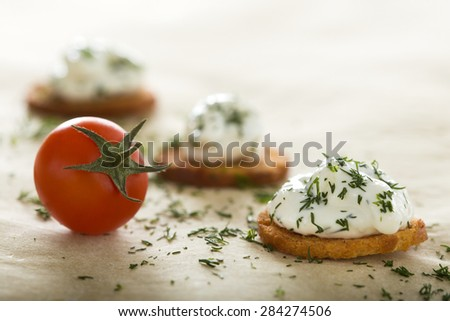 Fresh cream cheese spread with dill on bake rolls and cherry tomato - stock photo