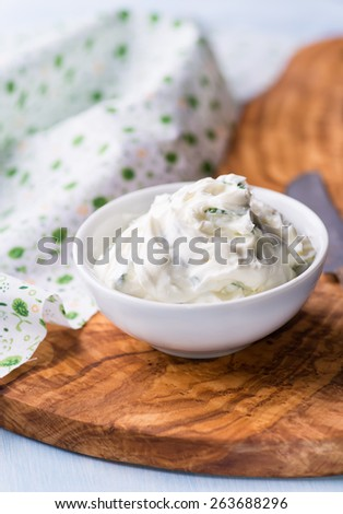 Fresh cream cheese spread with herbs in a bowl, selective focus
