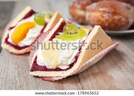 Fresh cream coloured Eclair cookie with exotic fruits on the old table in the background donuts - natural light