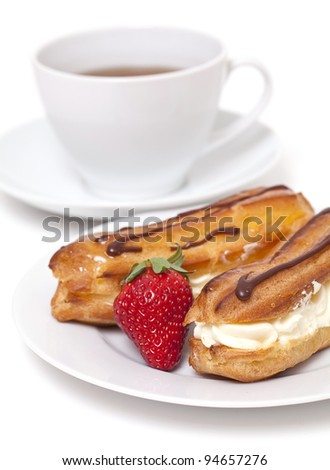 fresh cream puff with whipped cream and strawberry and cup of tea
