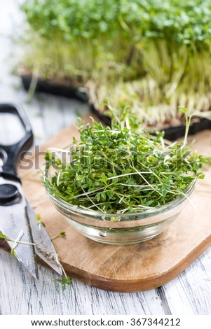 Fresh Cress (close-up shot) on rustic wooden background