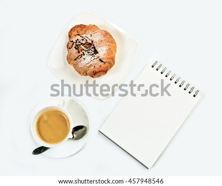 Fresh croissant, notepad  and coffee on white background. Top view. - stock photo