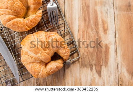 Fresh croissants on old wooden table background