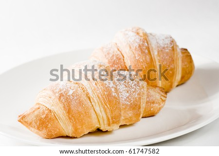 fresh croissants on white plate with powdered sugar - stock photo